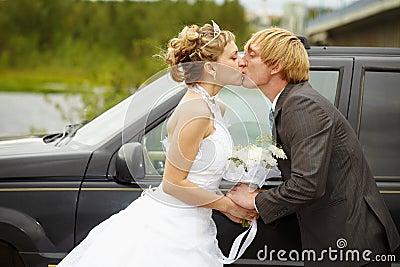 Bride and groom kissing near a car