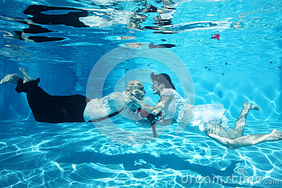 Bride and groom kissing underwater wedding diving red flowers