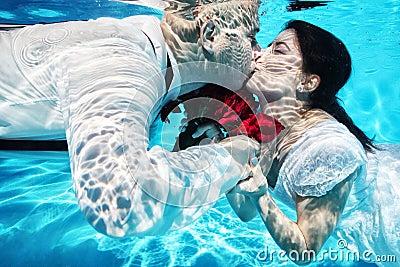Bride and groom kissing underwater wedding diving red flowers