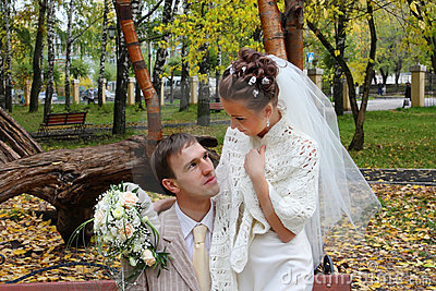 Bride and groom look at each other in autumn park