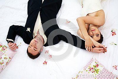 Bride and groom lying in bedroom with orchids
