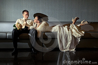 Bride and groom lying in a stylish lounge
