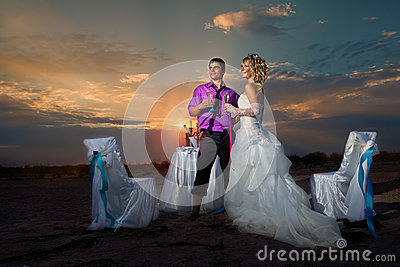 Bride and groom making at sunset