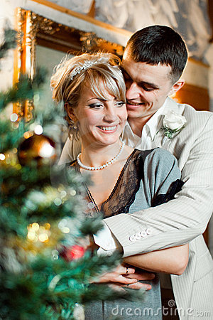 Bride and groom near christmas tree