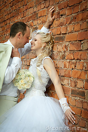 Bride and groom near the wall