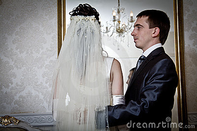 Bride and groom next to the mirror