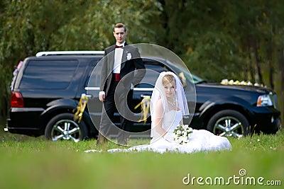 Bride and groom next to wedding car