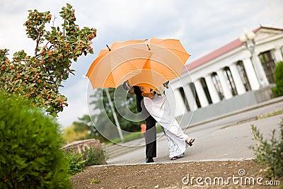 Bride and groom with orange umbrellas