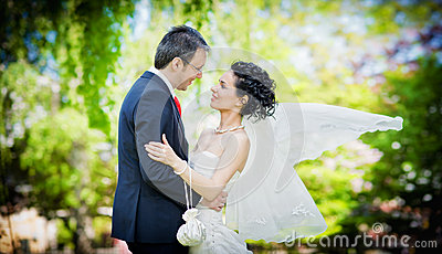 Bride and groom in a park kissing on green backgro