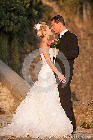 Bride and groom in a park outdoor at sunset