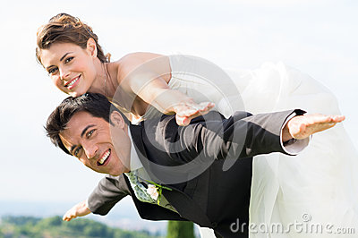 Bride and groom piggyback
