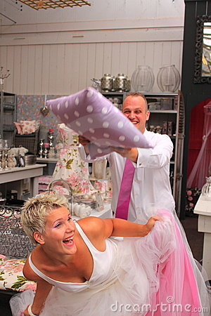 Bride and groom playing with pillow