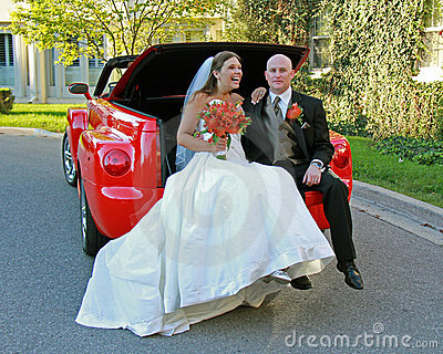 Bride and Groom Posing in Convertible Red Truck