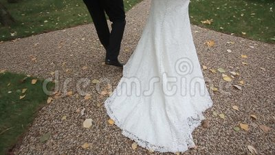 Bride and groom are on the road. Slow motion. Bride and groom are on the path of decorative street, bride and groom on the wedding day, bride in elegant gown and