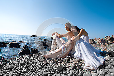 Bride and groom on sea coast