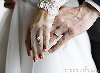 Bride and Groom Showing Their Engagement Wedding Rings on Hands Stock Photo