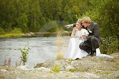 Bride and groom sit on riverbank