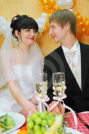 Bride and groom sitting at banquet table