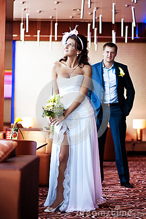 Bride and groom are standing in a bright room