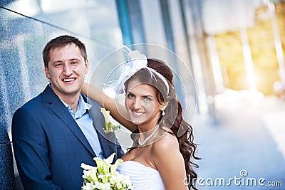 Bride and groom is standing granite wall