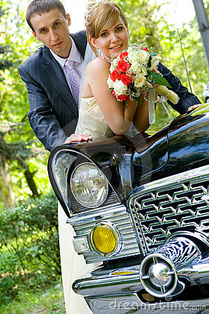 Bride and groom standing near wedding car