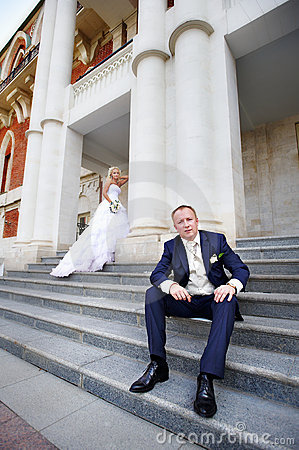 Bride and groom on steps of palace