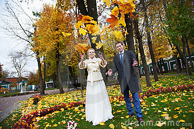 Bride and groom throw maple leaves