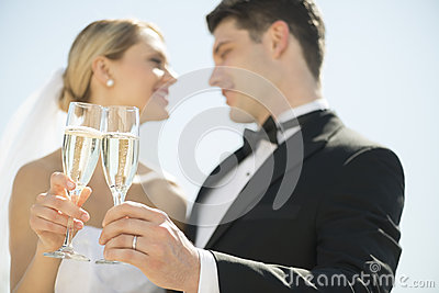 Bride And Groom Toasting Champagne Flutes Against Sky