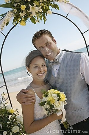 Bride and Groom under archway on beach