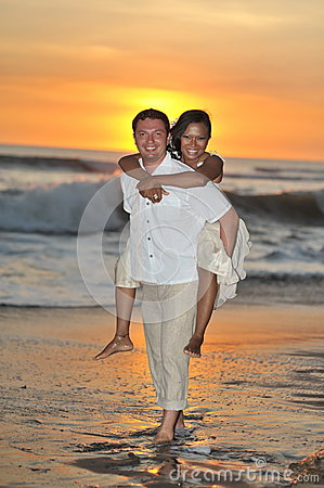 Bride and groom walking barefoot on beach