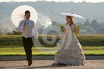 Bride and groom walking outside in sun with umbrel