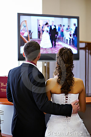 Bride and groom watch the video of his wedding