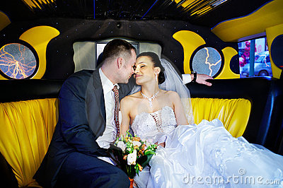 The bride and groom in a wedding limousine