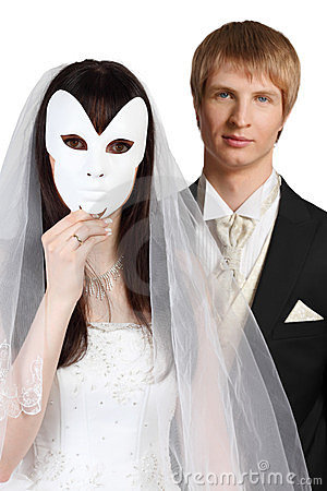 Bride hid face behind mask; groom stands behind