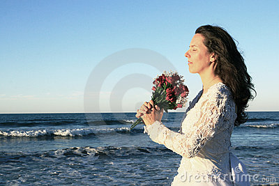 Bride holding bouquet by ocean