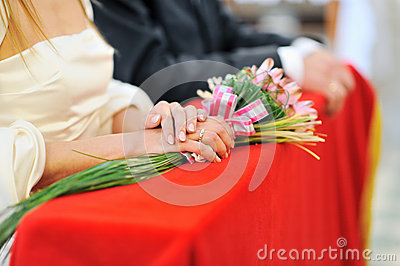 Bride holding bouquet during wedding ceremony