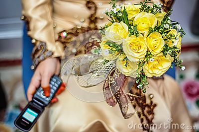 Bride holding flower and handphone
