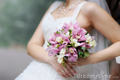 Bride holding pink wedding flowers bouquet
