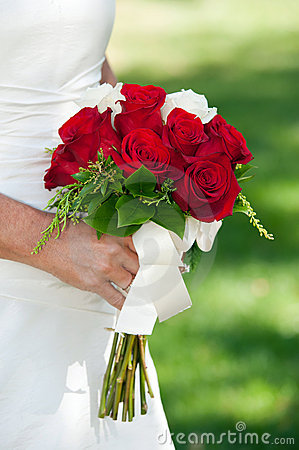Bride holding red rose bouquet