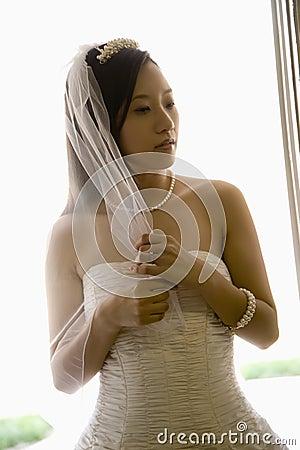 Bride holding veil.