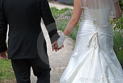 Bride and husband walk hand in hand