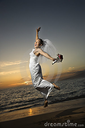 Bride jumping on beach.