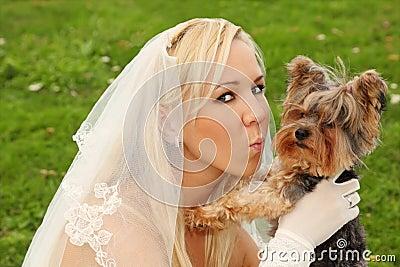 Bride keeps and kisses small dog
