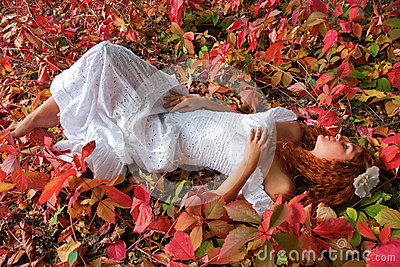 Bride lying among red leave