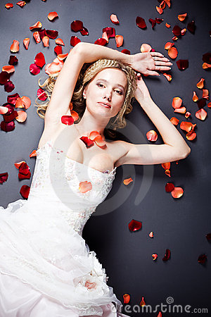 Bride lying among rose petals