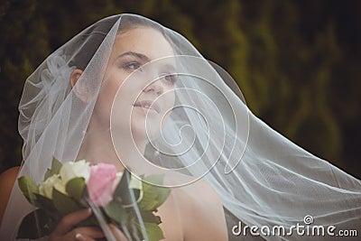 Bride portrait over green trees outdoor