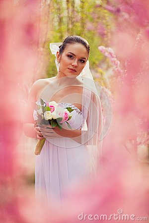 Bride portrait over pink cherry trees outdoor