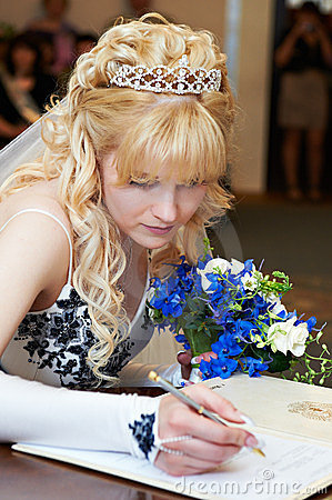 Bride puts signature on registration of marriage