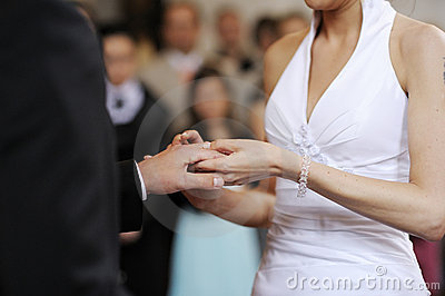 Bride putting a ring on a groom s finger