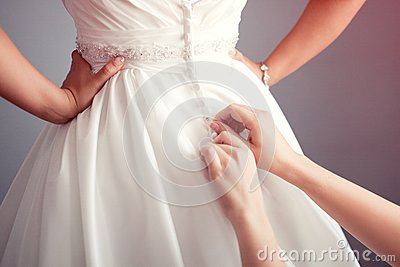 Bride putting on a wedding dress